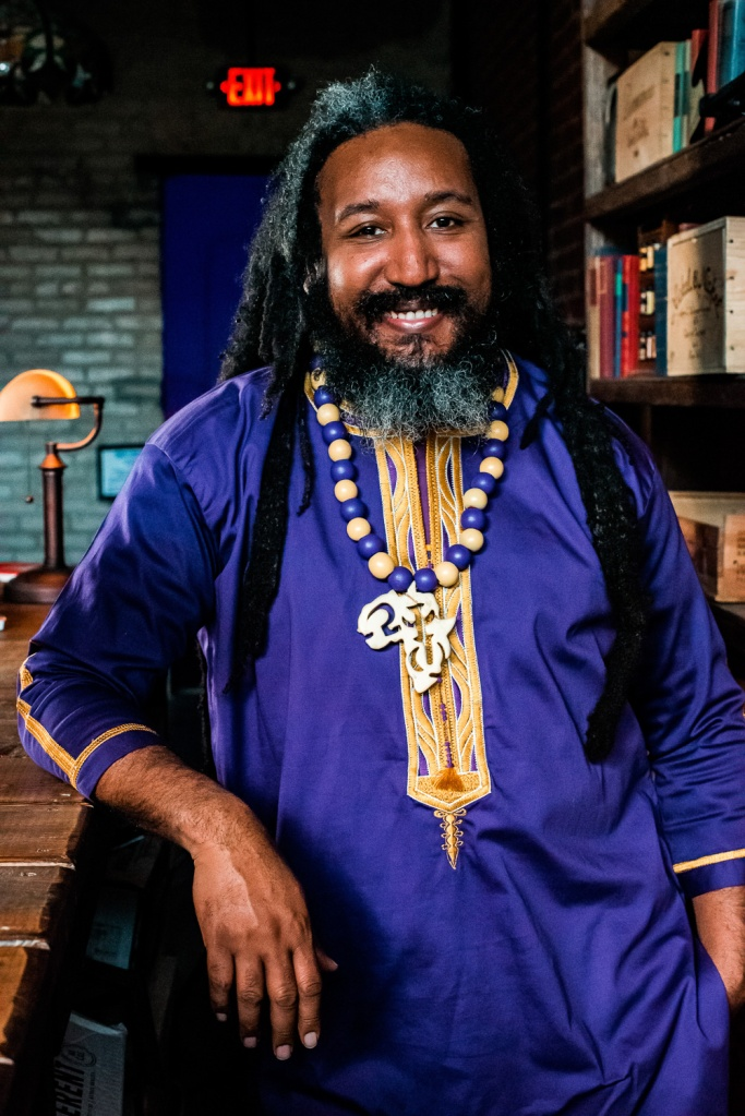 Portrait of Dr. Malik Boykin. Malik stands as a smiling black man with dreadlocks, wearing purple regalia and an African necklace in a library.